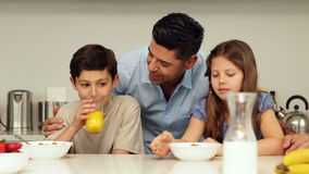 Padre que charla con sus niños que desayunan metrajes