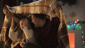 Padre que cuenta la historia impresionante de Navidad para la niña que se sienta debajo de la tela escocesa acogedora metrajes
