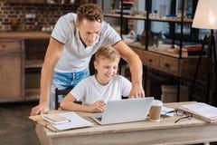 Padre que cuida que ayuda a su hijo con los ajustes del ordenador portátil Fotografía de archivo libre de regalías