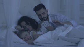 Padre que cuida blando que abraza y que besa a su familia antes de caer dormida en la noche almacen de video