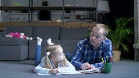 Padre que cuida con la muchacha preescolar que estudia en casa almacen de metraje de vídeo