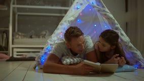 Padre que cuida que lee un libro con su hija en casa almacen de video