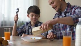Padre que cuida que prepara los copos de maíz para el hijo por mañana, desayuno de la familia en casa almacen de video
