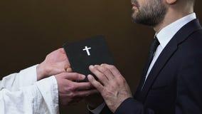 Padre que dá a Bíblia Sagrada do homem de negócio contra o fundo preto, cristandade video estoque