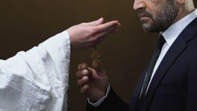Padre que dá a cruz de madeira política masculina contra o fundo preto, cristandade filme