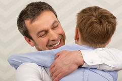 Padre que da abrazos al estimado hijo Imágenes de archivo libres de regalías