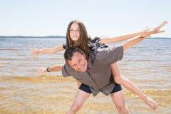 Padre que da a cuestas paseo a la hija del adolescente en la playa Imagen de archivo libre de regalías