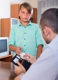 Padre que da efectivo al hijo adolescente Foto de archivo