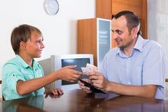 Padre que da efectivo al hijo adolescente Imagen de archivo libre de regalías