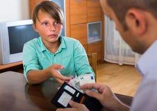 Padre que da efectivo al hijo adolescente Foto de archivo libre de regalías