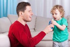 Padre que da a hijo una botella con la bebida Fotografía de archivo