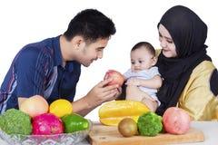 Padre que da una manzana al bebé Imagenes de archivo