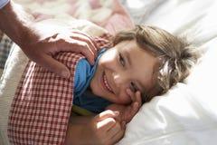 Padre que despierta al muchacho joven dormido en cama imagen de archivo libre de regalías