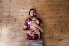 Padre que detiene al bebé recién nacido, fondo de madera imagen de archivo libre de regalías