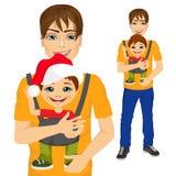 Padre que detiene al niño pequeño con el portador de bebé Foto de archivo