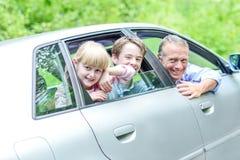 Padre que disfruta de la impulsión del coche con sus niños Foto de archivo