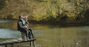 Padre que enseña a su hijo a la pesca en el lago Tirado en la epopeya roja 4K metrajes
