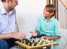 Padre que enseña a su hijo que juega a ajedrez Fotografía de archivo