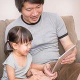 Padre que enseña a su niña a leer Foto de archivo