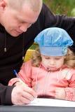 Padre que enseña a la pequeña hija a escribir Fotografía de archivo