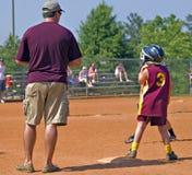 Padre que entrena el beísbol con pelota blanda de la hija foto de archivo libre de regalías