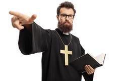 Padre que guarda uma Bíblia e apontar foto de stock