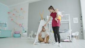 Padre que habla en el teléfono que se sienta en choza del bebé almacen de video