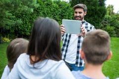 Padre que hace clic la imagen de la familia de la tableta digital en parque Fotografía de archivo libre de regalías