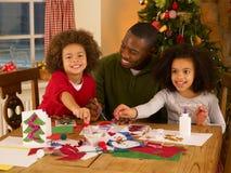 Padre que hace tarjetas de Navidad con los niños Fotos de archivo libres de regalías