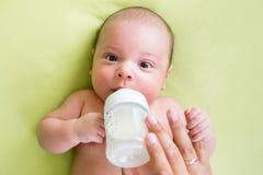 Padre que introduce a su niño del bebé de la botella Imagenes de archivo