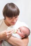 Padre que introduce a su niño del bebé de la botella Fotografía de archivo libre de regalías