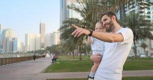 Padre que juega con los hijos en el verano alrededor de las palmeras y de los edificios almacen de metraje de vídeo