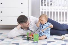 Padre que juega con su bebé fotos de archivo