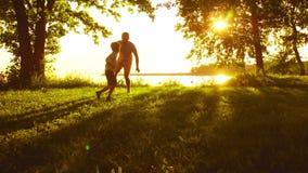 Padre que juega con su hijo cerca del mar Colores calientes de la puesta del sol o de la salida del sol Padres de amor y niños he metrajes