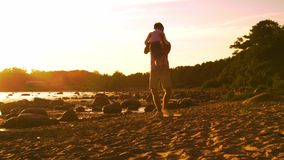 Padre que juega con su hijo cerca del mar Colores calientes de la puesta del sol o de la salida del sol Padres de amor y niños he almacen de metraje de vídeo