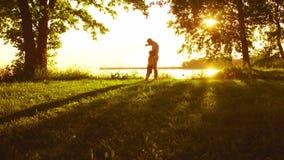 Padre que juega con su hijo cerca del mar Colores calientes de la puesta del sol o de la salida del sol Padres de amor y niños he almacen de video