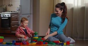 Padre que juega a juegos con su niño para desarrollar capacidades finas de motor metrajes