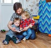 Padre que lee un libro a los niños Foto de archivo