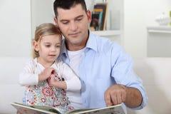 Padre que lee una historia foto de archivo