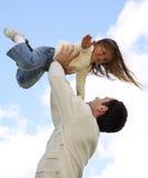 Padre que levanta a la pequeña hija Fotografía de archivo