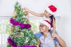 Padre que levanta a su hija cerca del árbol de navidad Fotografía de archivo