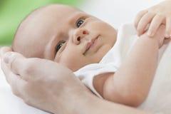 Padre que lleva a cabo las manos sonrientes jovenes del bebé Foto de archivo libre de regalías