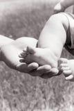 Padre que lleva a cabo pequeños pies Foto de archivo libre de regalías