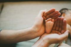 Padre que lleva a cabo su cabeza del ` s del bebé Imagenes de archivo