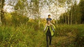 Padre que lleva a su hijo en hombros que camina a través de bosque y de alta hierba antes de puesta del sol en verano Cámara lent metrajes