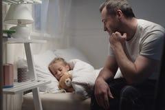 padre que mira a la pequeña hija adorable que duerme con el oso de peluche fotografía de archivo