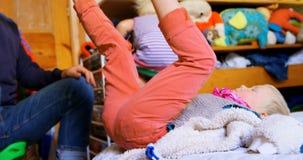 Padre que quita sus calcetines de los hijos en el dormitorio en casa 4k almacen de video
