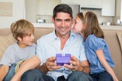 Padre que recibe el regalo de niños cariñosos imagenes de archivo