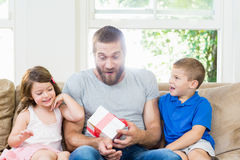 Padre que recibe un regalo de sus niños foto de archivo