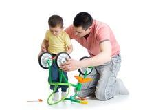 Padre que repara la bicicleta de los niños con su hijo Fotos de archivo libres de regalías